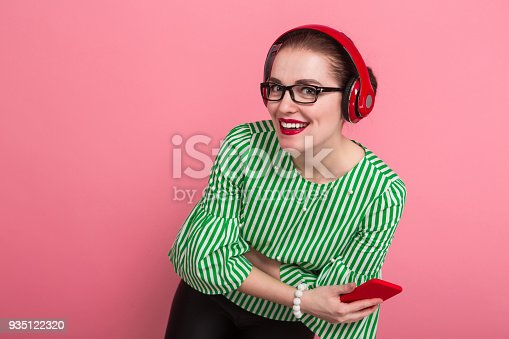 istock Businesswoman with phone and earphones 935122320