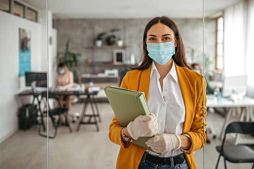 Portrait of businesswoman with protective gloves and face mask after returning back to work at office