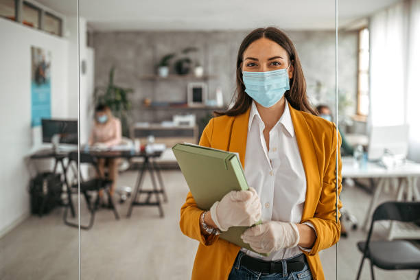 Businesswoman with protective gloves and face mask at office stock photo