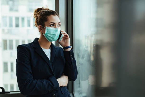 Businesswoman with protective mask talking on mobile phone by the window. stock photo