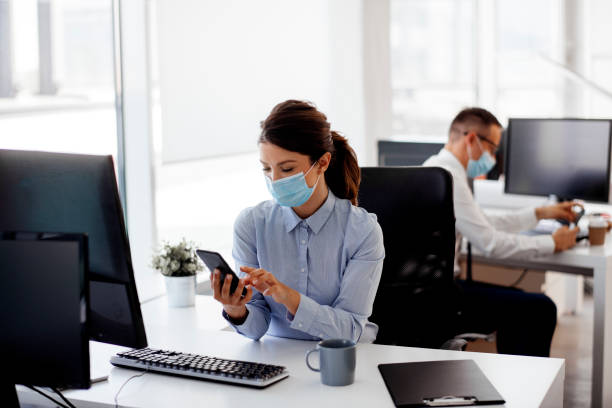Businesswoman with protective mask using a mobile phone stock photo stock photo