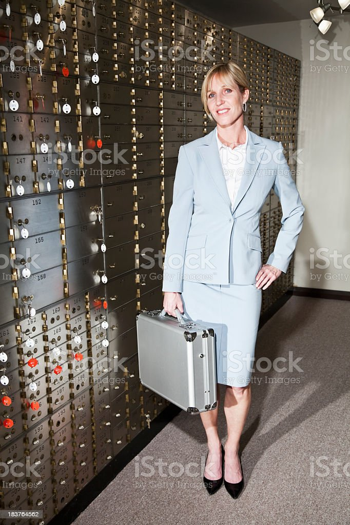 Businesswoman with safety deposit boxes stock photo