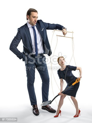 istock businesswoman with shovel in hands manipulated by boss isolated on white 817355534