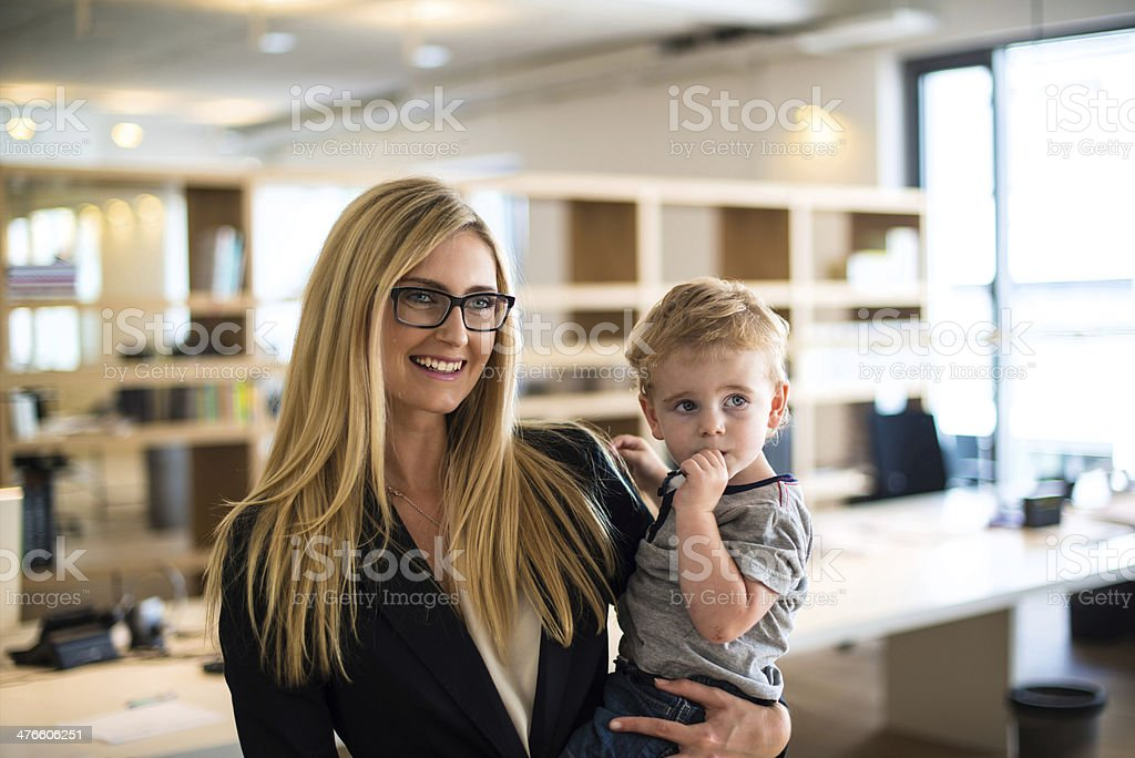 Businesswoman with small child in the office stock photo