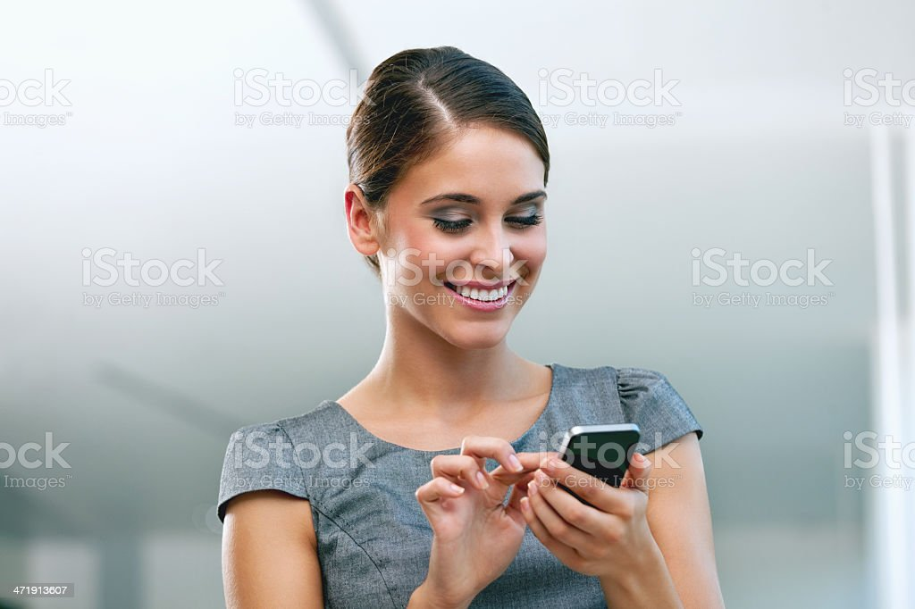 Businesswoman with smart phone Cheeful businesswoman using a smart phone. 20-24 Years Stock Photo