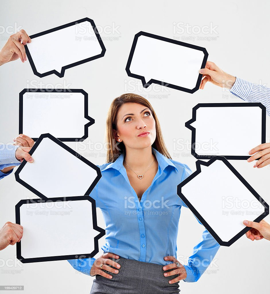 Businesswoman with speech bubbles Smirking businesswoman surrounded by many speech bubbles with copyspace, looking up. 25-29 Years Stock Photo