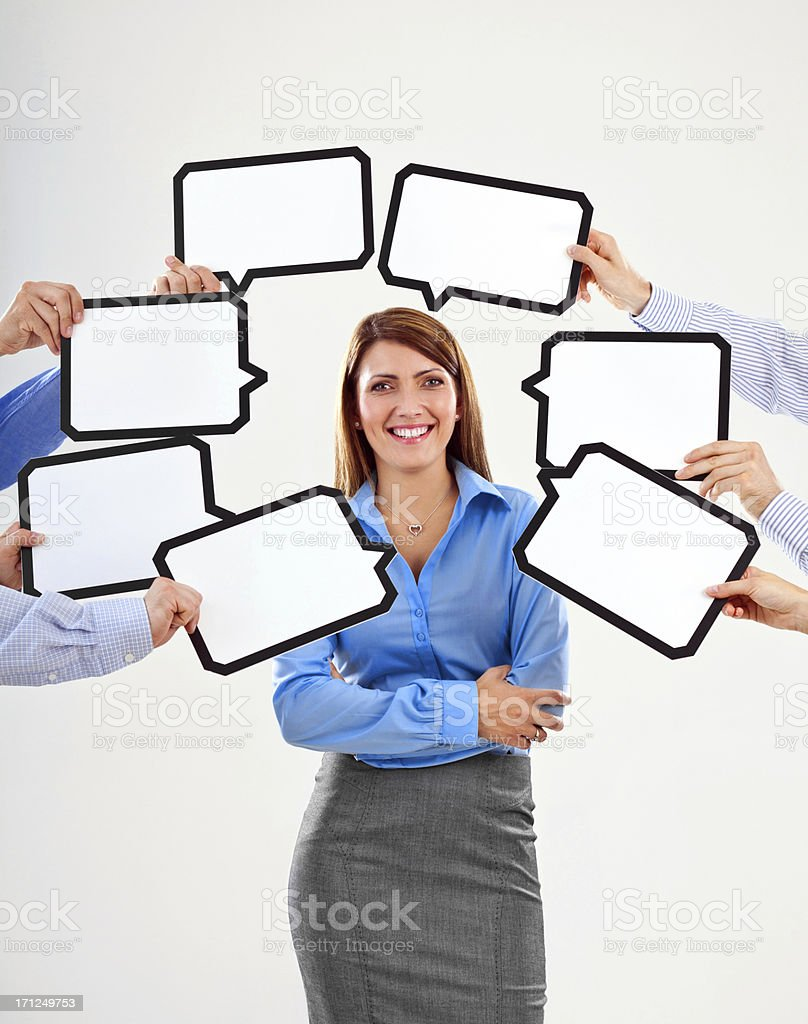 Businesswoman with speech bubbles Attractive businesswoman surrounded by many speech bubbles with copyspace, smiling at the camera. 25-29 Years Stock Photo