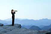 A businesswoman looks through a spyglass as she stands and looks out towards a series of mountain ridges that recede into the distance