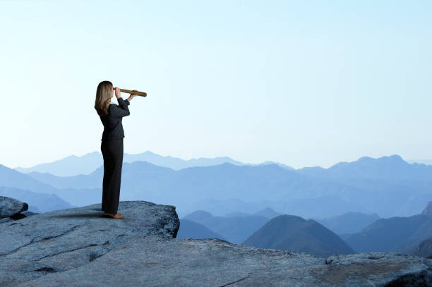 Businesswoman With Spyglass Looking Out Toward Mountain Range stock photo
