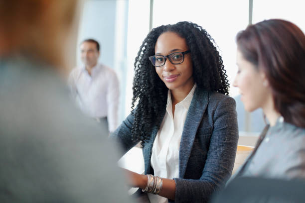 Businesswoman with staff in office meeting looking at camera stock photo