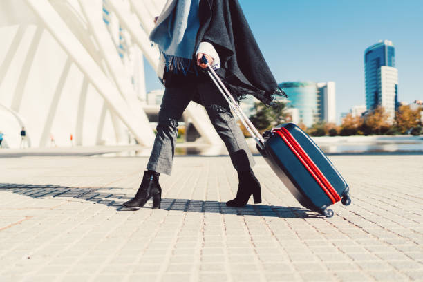 Businesswoman with suitcase hurrying for the flight Young woman just arriving in Spain and pulling a suitcase air stewardess stock pictures, royalty-free photos & images