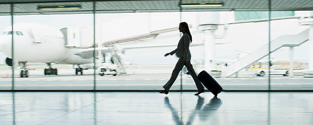 Businesswoman with suitcase in airport stock photo