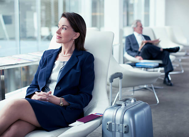 Businesswoman with suitcase waiting in airport stock photo