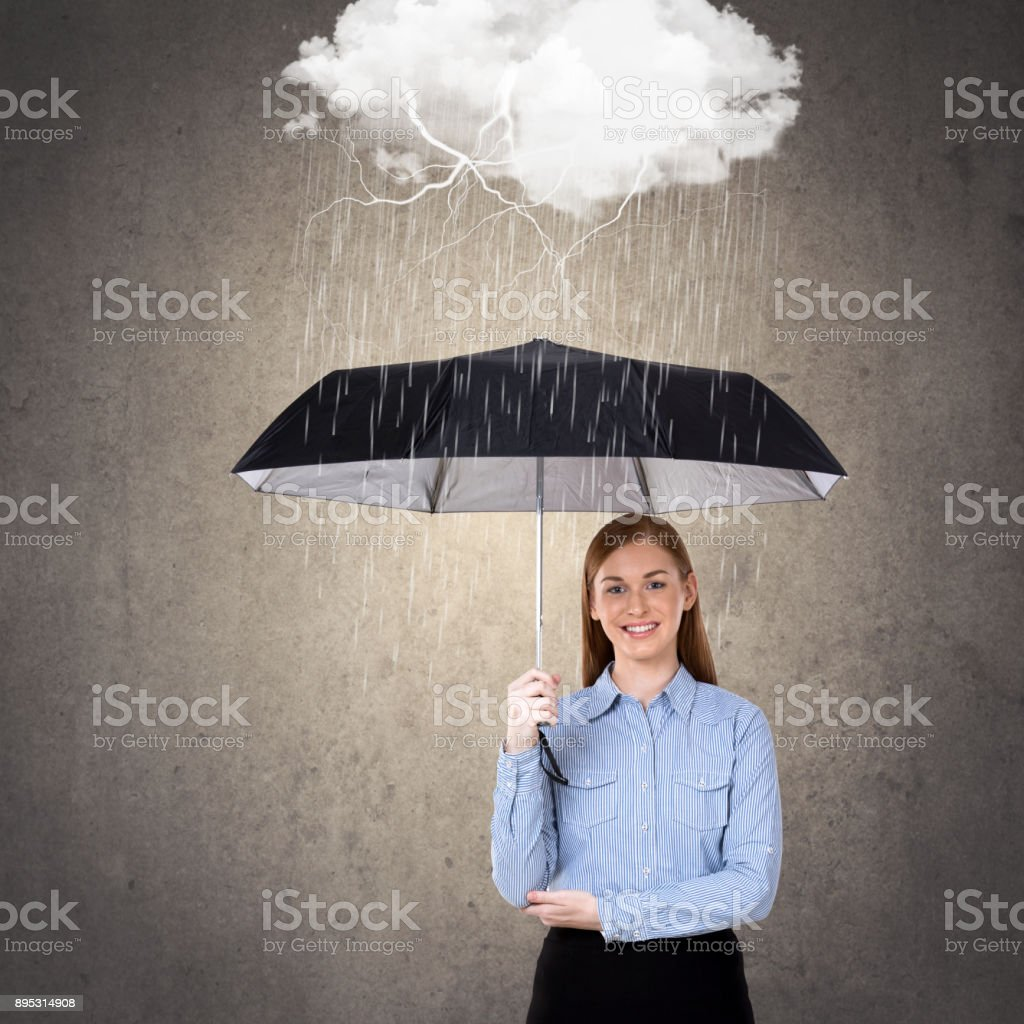 Portrait of businesswoman holding umbrella protecting herself from...