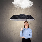 Portrait of businesswoman holding umbrella protecting herself from rain storm