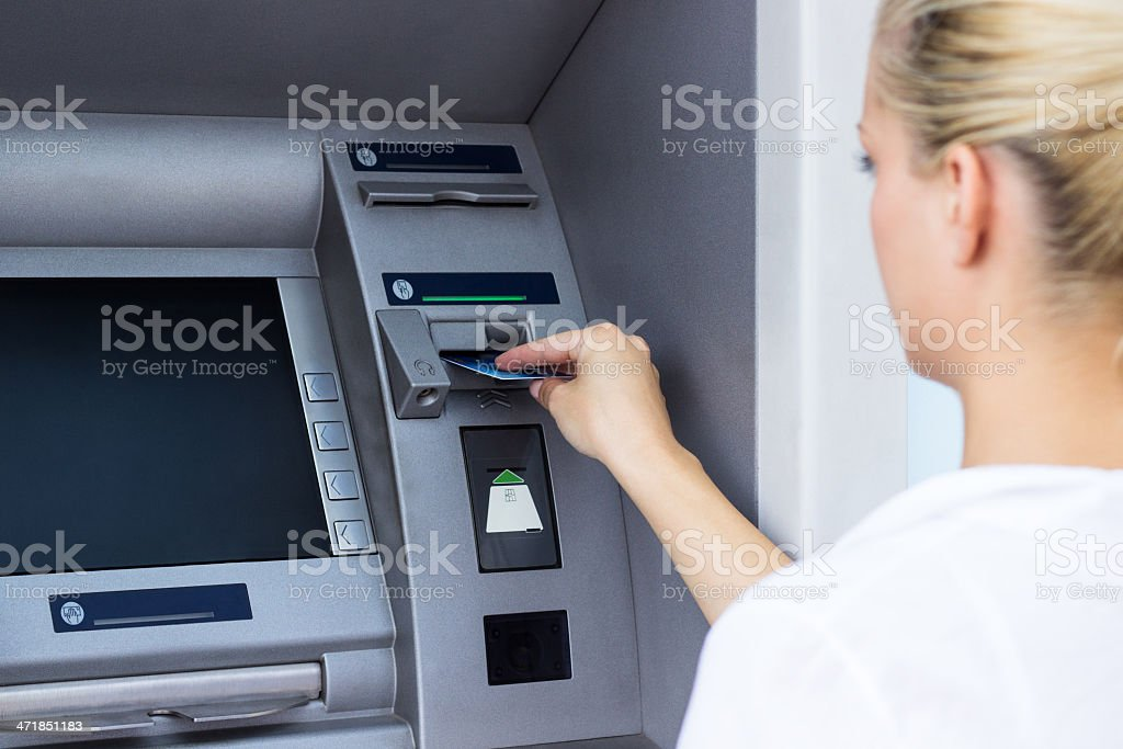 Businesswoman withdrawing money from credit card at ATM stock photo