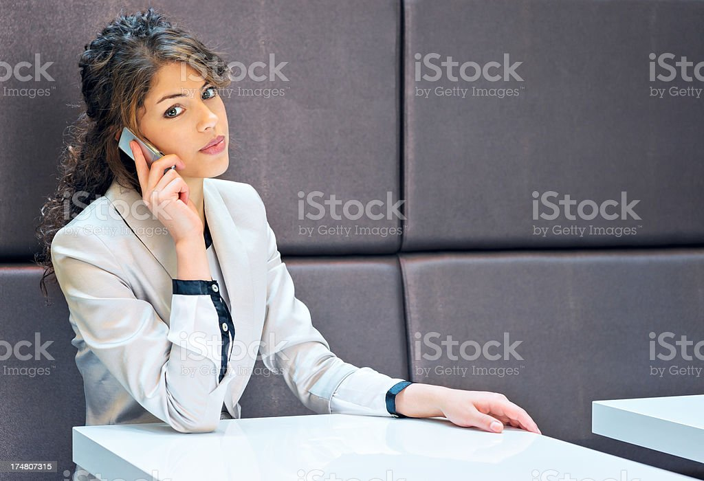 Businesswoman working and communicating on cellphone stock photo