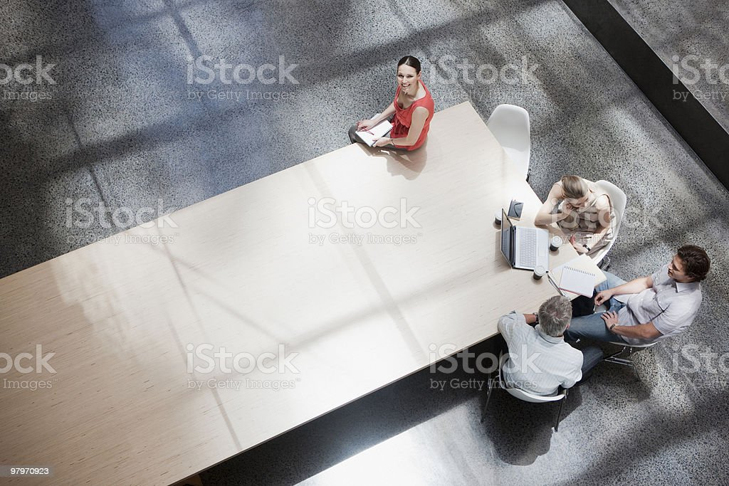 Businesswoman working apart from co-workers at conference table royalty-free stock photo