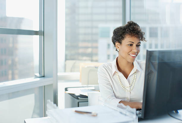Businesswoman working at desk in office  using computer stock pictures, royalty-free photos & images