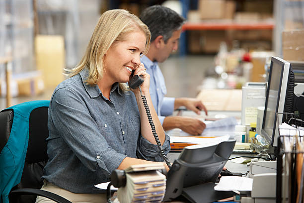 Businesswoman Working At Desk In Warehouse stock photo