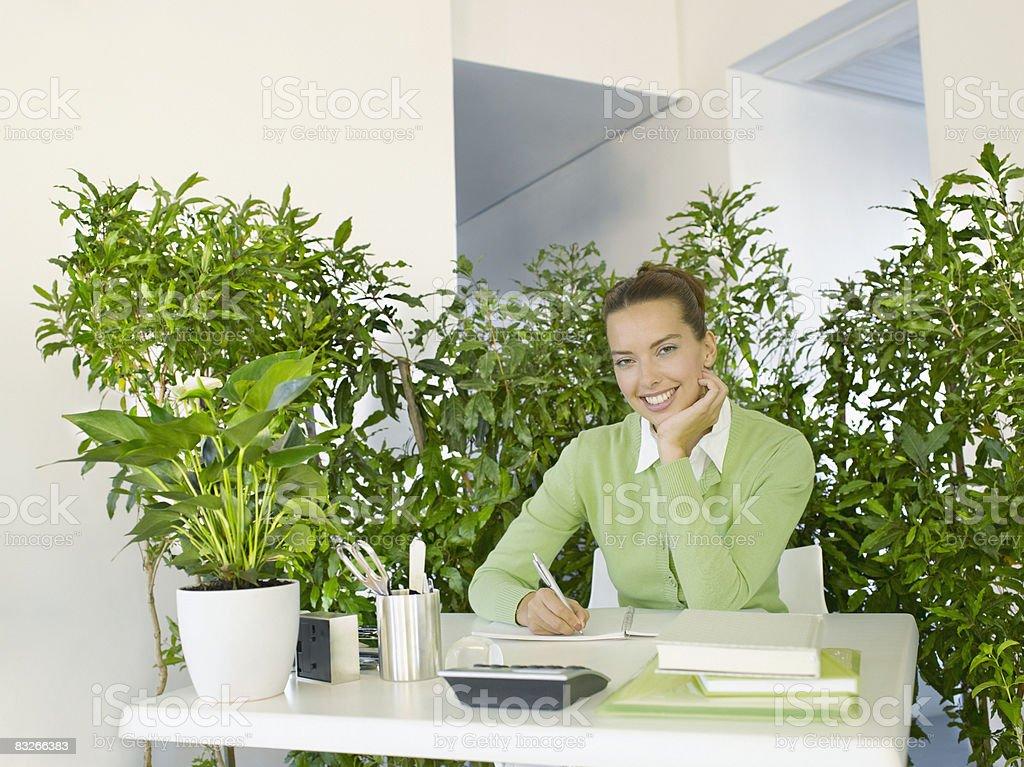 Empresaria de trabajo con escritorio, rodeado de plantas foto de stock libre de derechos