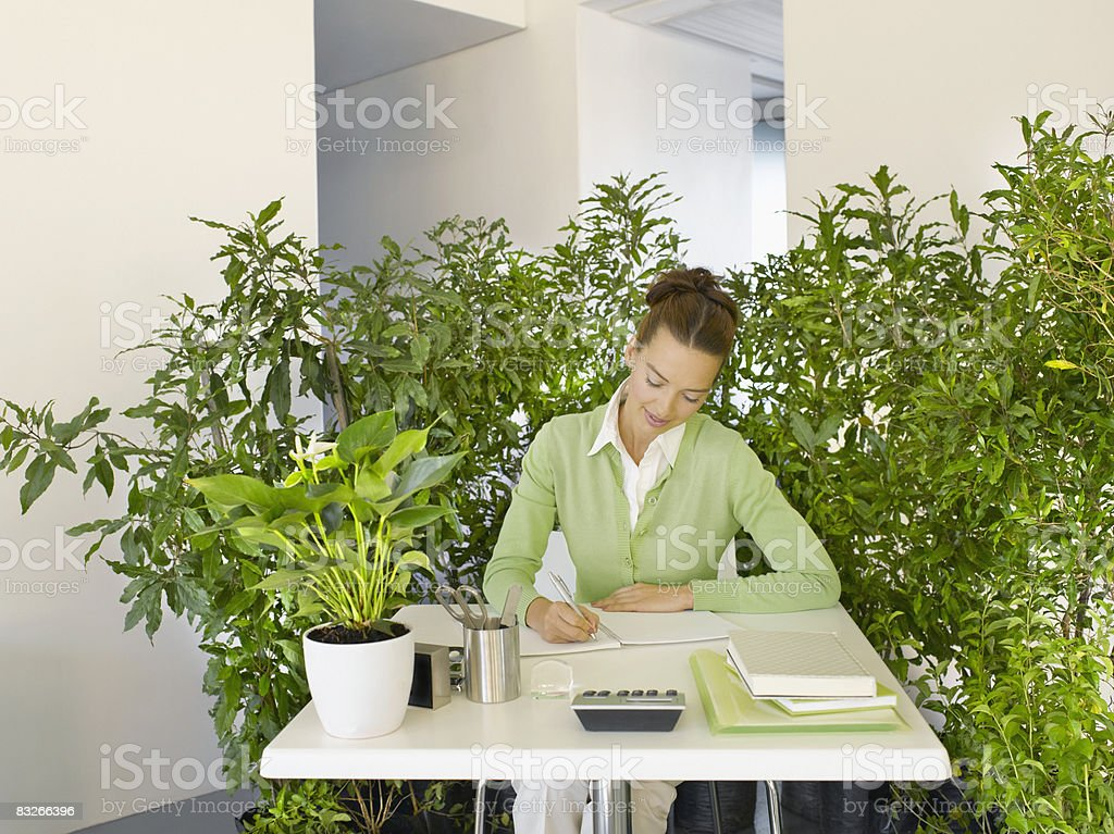 Businesswoman working at desk surrounded by plants royalty free stockfoto