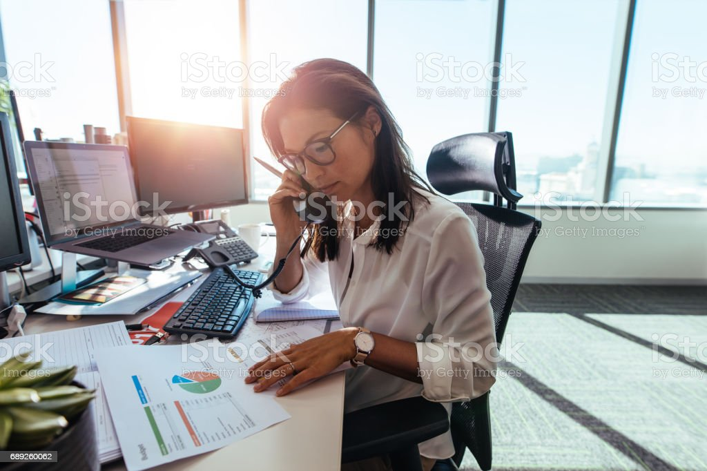 Businesswoman working at her desk in office. stock photo