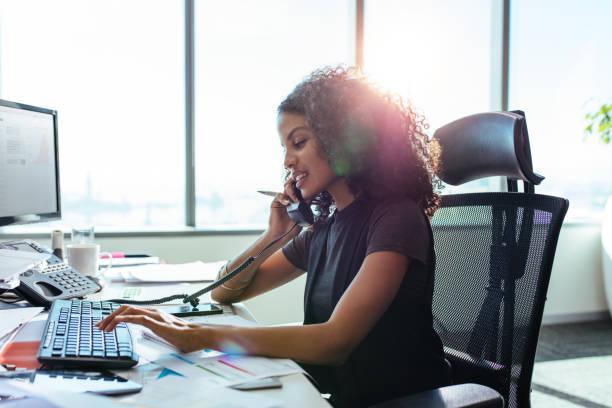 zakenvrouw werken bij haar balie in kantoor. - business woman phone stockfoto's en -beelden