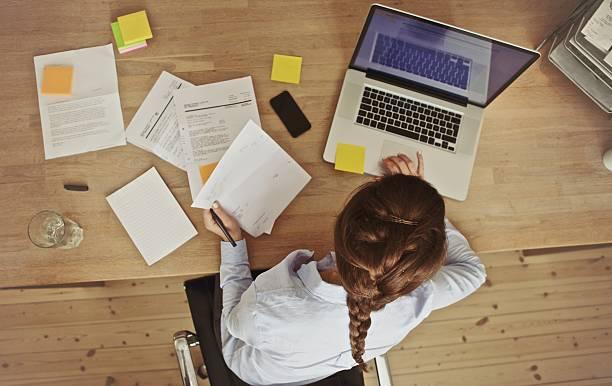 geschäftsfrau arbeiten an ihrem büro-schreibtisch mit dokumenten und laptop - schreibtischunterlagen stock-fotos und bilder