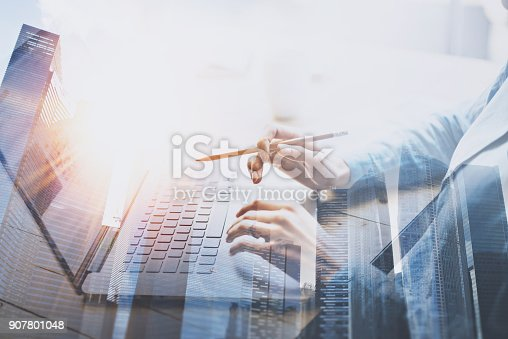 istock Businesswoman working at modern office on laptop.Young woman working at the wooden table with notebook.Blurred background.Double exposure horizontal. 907801048