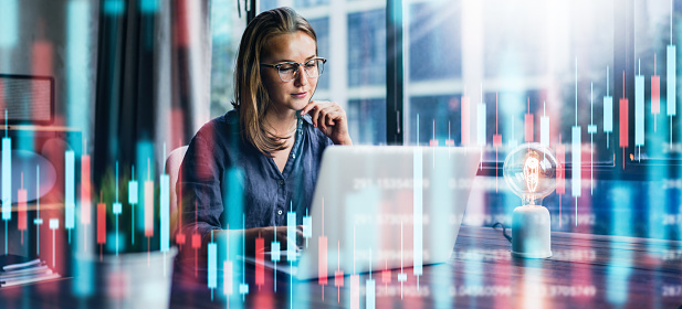 Young woman working at modern office.Technical price graph and indicator, red and green candlestick chart and stock trading computer screen background. Double exposure. Trader analyzing data