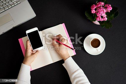 831932306 istock photo Businesswoman working at office and she is writing to blank notebook. 1134428668