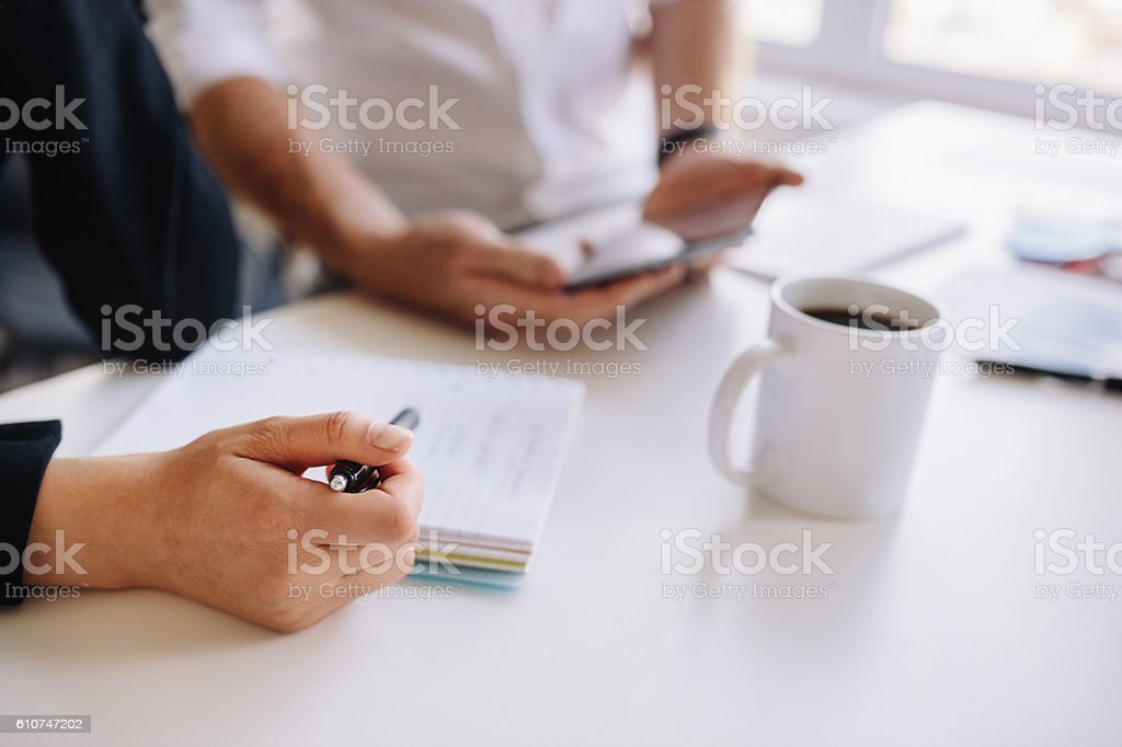Businesswoman working at office with associate stock photo