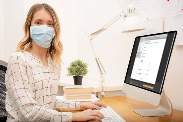Businesswoman working from home, wearing protective mask stock photo