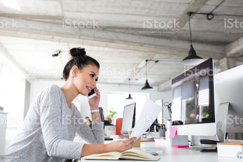 Businesswoman working in a modern office Portrait of beautiful young woman talking on phone at office with a document in hand. Businesswoman working in a modern office. Adult Stock Photo
