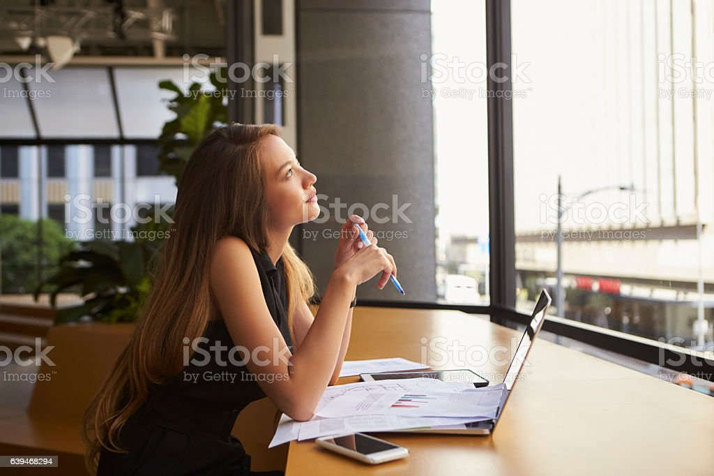 Businesswoman working in an office looking out of the window stock photo