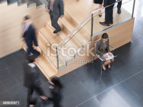483635979 istock photo Businesswoman working in busy office corridor 483635971