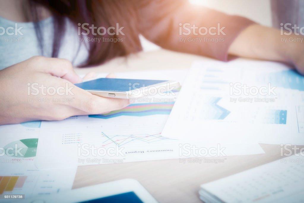 Ofiste çalışan ve iş diyagramları tablo ile smartphone kullanarak bir işkadını. Finans ofis işyeri. - Royalty-free Adamlar Stok görsel
