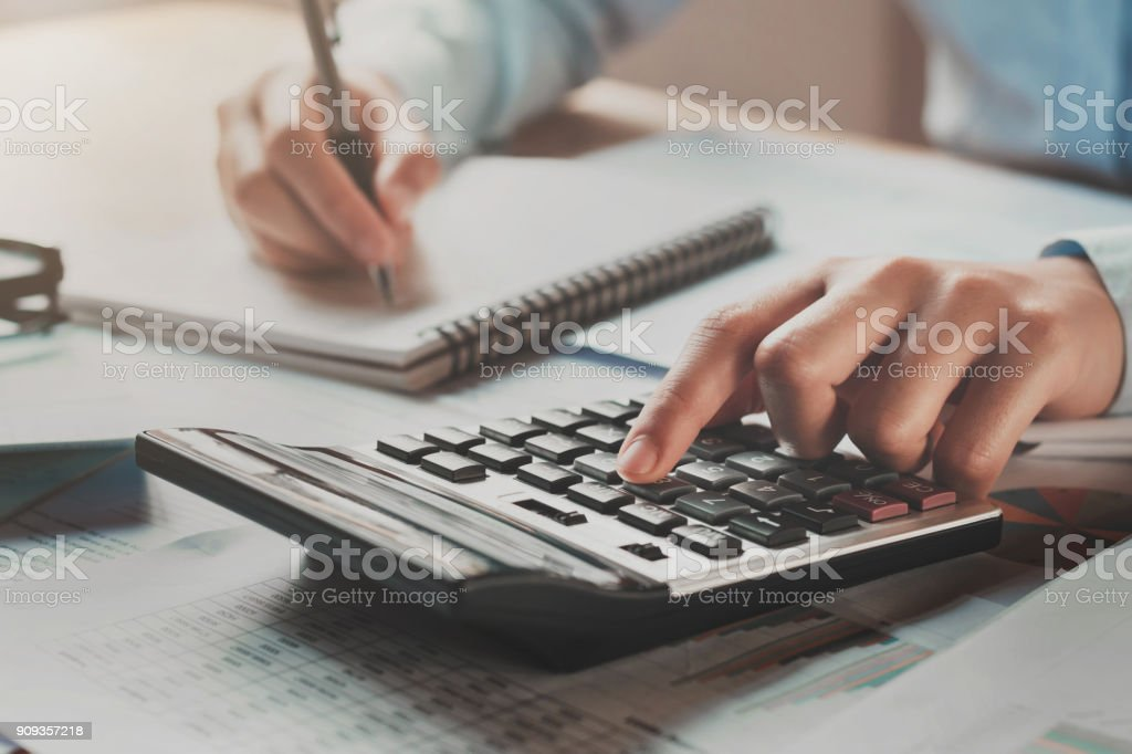 businesswoman working in office on desk using calculator and pen with sunshine stock photo