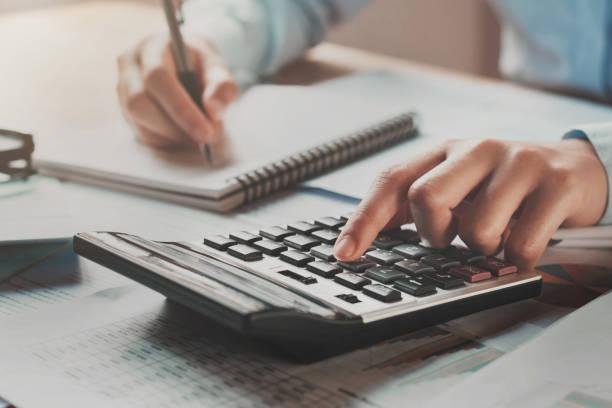 Geschäftsfrau, die Arbeiten im Büro am Schreibtisch mit Taschenrechner und Kugelschreiber mit Sonnenschein – Foto