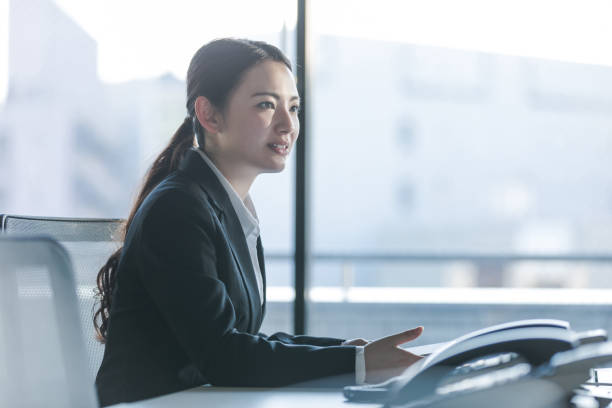 Businesswoman working in the office. Positive workplace concept. Businesswoman working in the office. Positive workplace concept. japanese ethnicity stock pictures, royalty-free photos & images