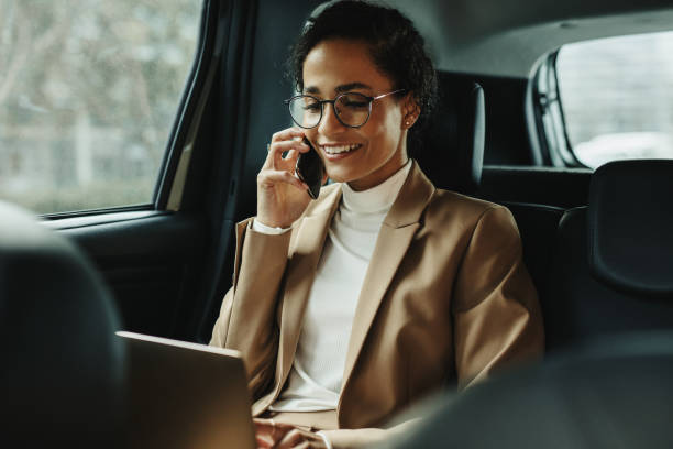 Businesswoman working inside a cab on the way to work stock photo
