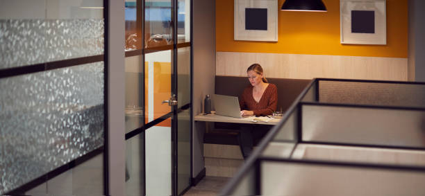 Businesswoman Working Late In Open Plan Office Using Laptop Businesswoman Working Late In Open Plan Office Using Laptop letterbox format stock pictures, royalty-free photos & images