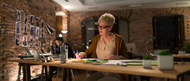 geschäftsfrau, die überstunden im büro - produktdesigner stock-fotos und bilder