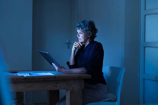 mulher de negócios trabalhando tarde - senior business woman tablet imagens e fotografias de stock
