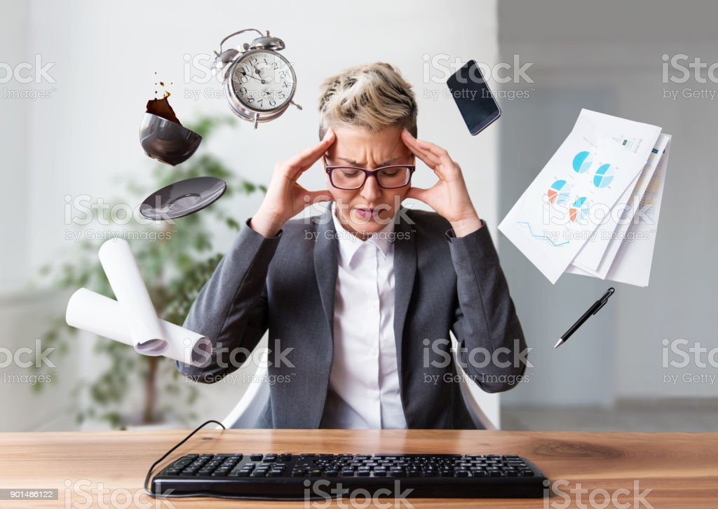 Businesswoman working on a laptop, under pressure stock photo