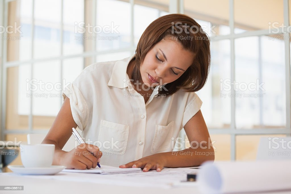 Businesswoman working on blueprint in office stock photo
