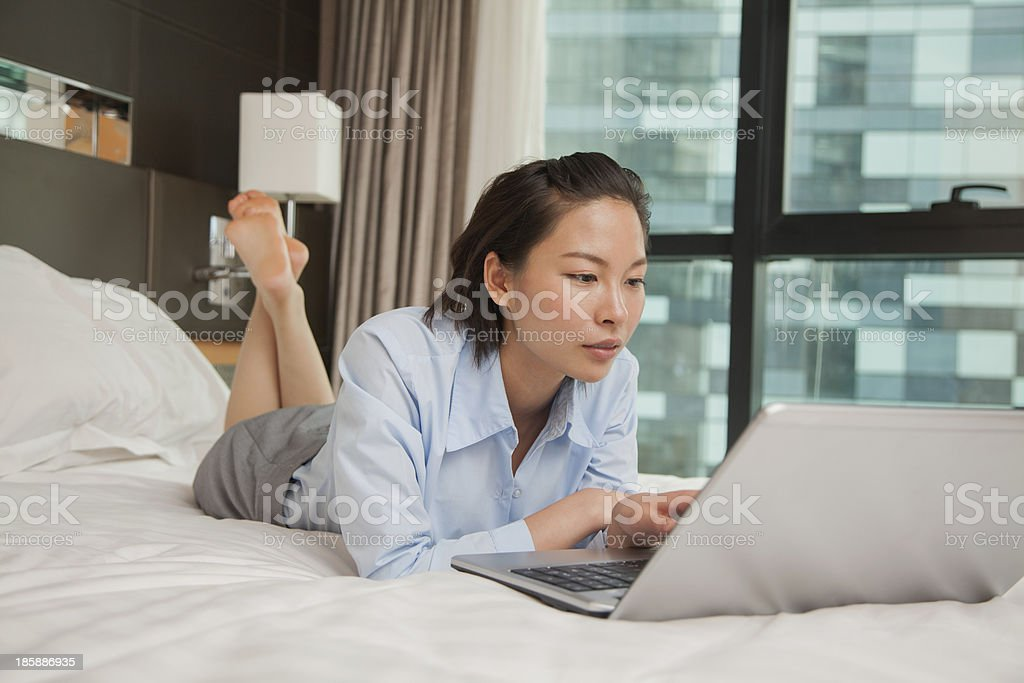 Businesswoman working on her laptop in the bed stock photo