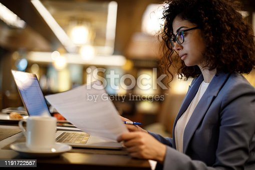 Businesswoman working on laptop at a cafe