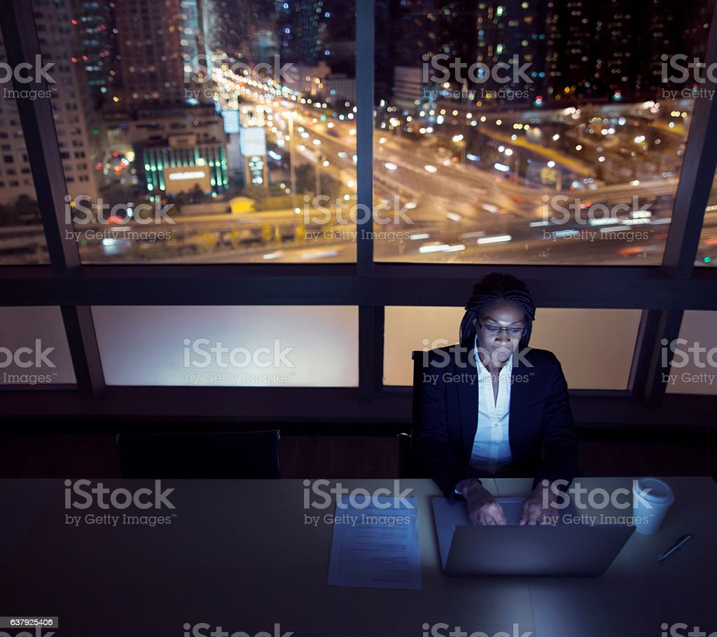 Businesswoman working on laptop at night in office downtown stock photo